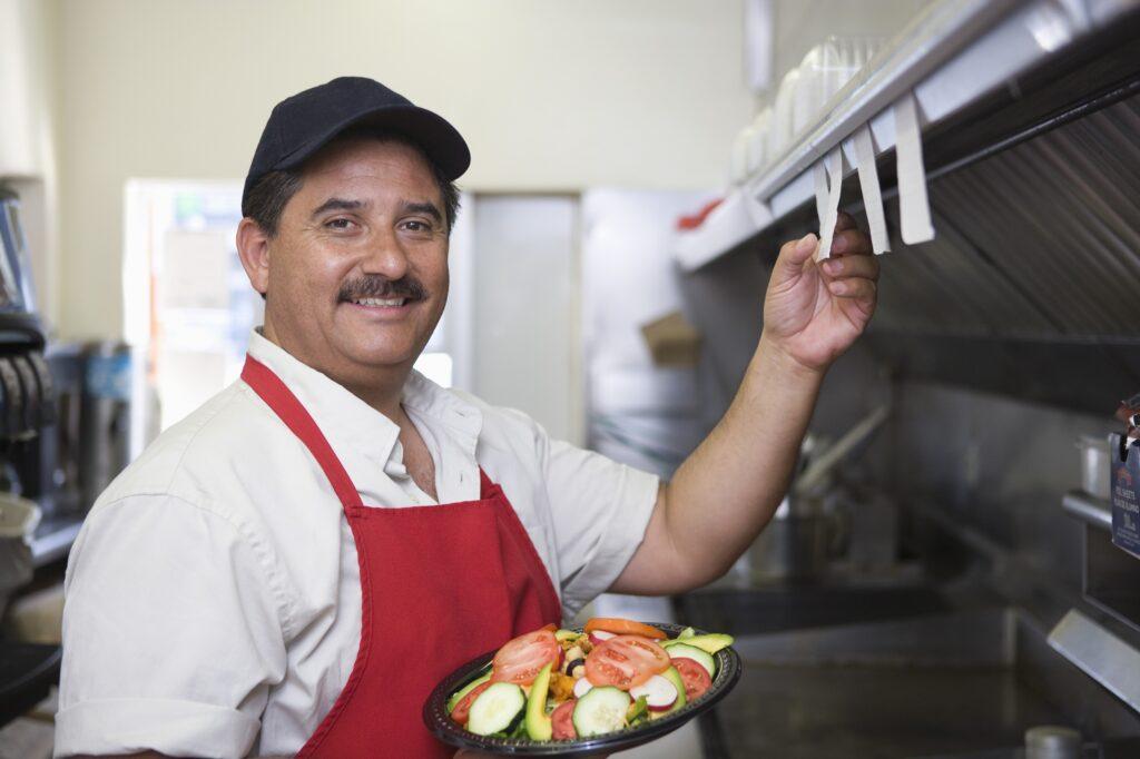 kucharz korzystający z wyposażenia gastronomicznego