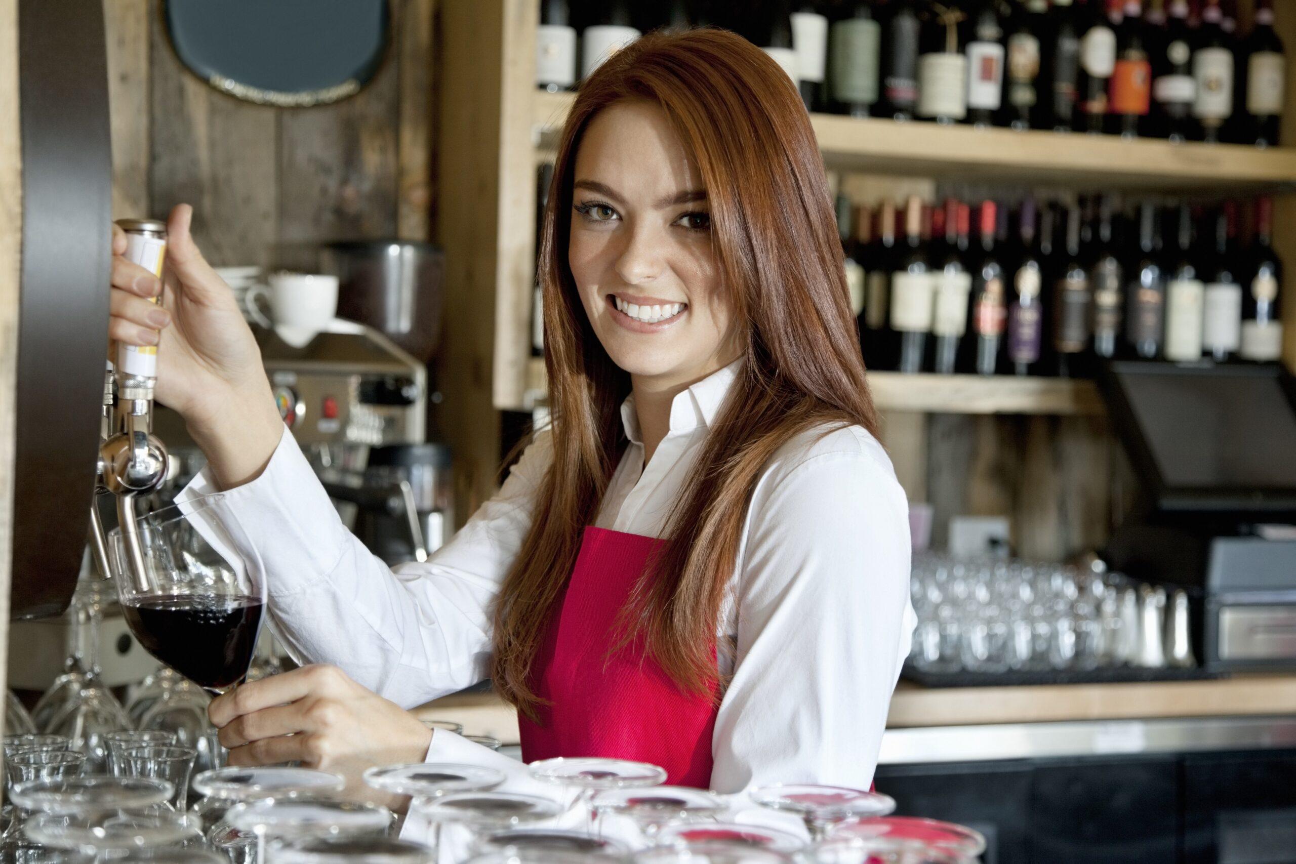 barmanka otwierająca wino otwieraczem do butelek